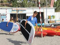 Young man with the SUP board towards the sea