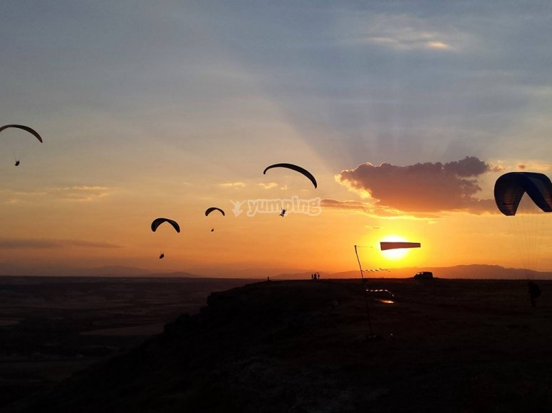 Several paragliders with the sunset