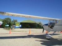 Avioneta frente a las puertas del hangar