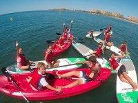 Chavales en los kayaks y sobre las tablas