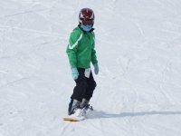 Asolescente haciendo snowboard