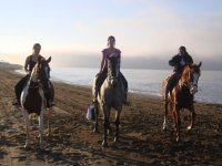 Three girls on the horsebacks in the beach