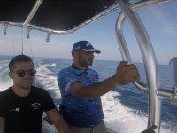 Dos amigos navegando en uno de los barcos alquilados