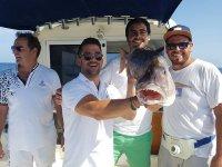 Hombres mostrando la boda de su gran pesca