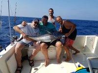 Grupo de amigos posando con un gran pez