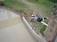Chica haciendo puenting sobre el rio