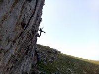 Sujetandose a la roca al atardecer