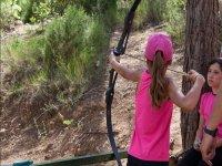 Alumna con gorra rosa disparando con el arco