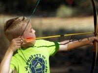 Peque tirando con arco en el campamento bilingue