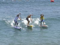 Three people paddle surf