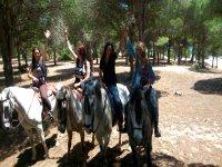 Chicas levantando la mano a caballo