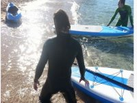 arrodillado en la arena paddlesurf