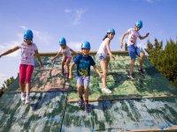 Niños bajando la rampa de madera en la pista americana