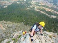 Chica ascendiendo una ferrata en Valencia