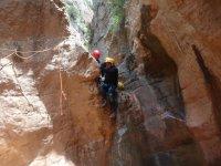 Scendere giù dalla parete rocciosa