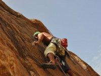 Apoyandose en los dedos en la pared de roca