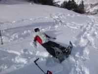 Tumbada en la nieve con las raquetas puestas