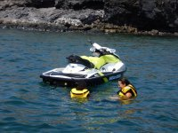 Riendose en el mar junto a la moto