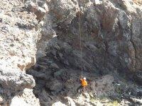 Hombre descendiendo por el acantilado