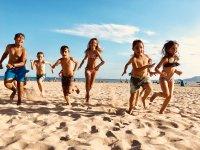 Chicos y chicas disfrutando de las actividades en la playa