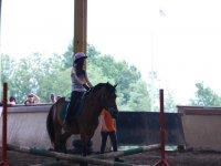 Chica principiante montada en Poni con casco