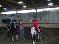 Dos chicas montadas en ponis con las manos hacia arriba