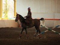 Hombre con gabardina montado a caballo
