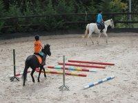 Joven en caballo practicando los saltos