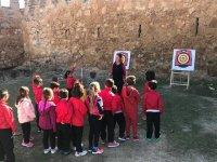 Des enfants tentent leur chance avec le tir à l'arc