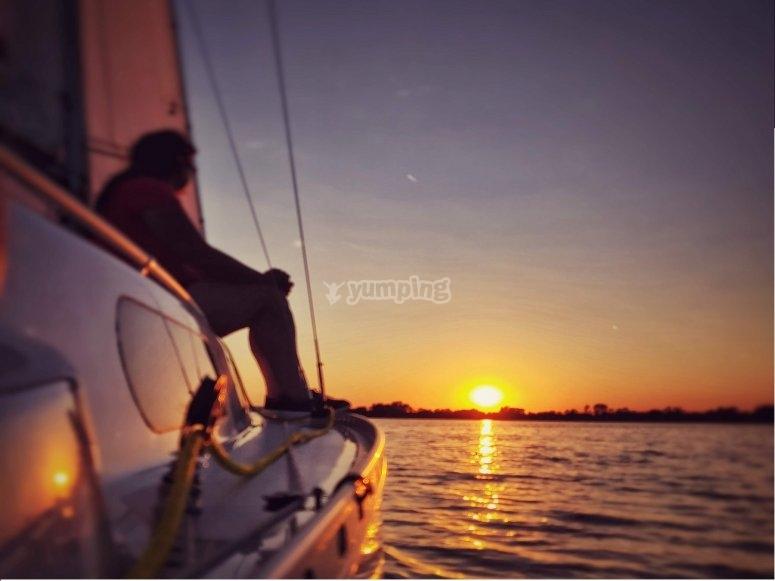 Mujer disfrutando de la puesta de sol desde el barco