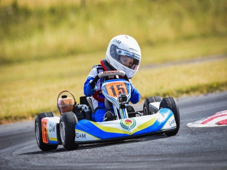 Niño tomando la curva del circuito con el kart