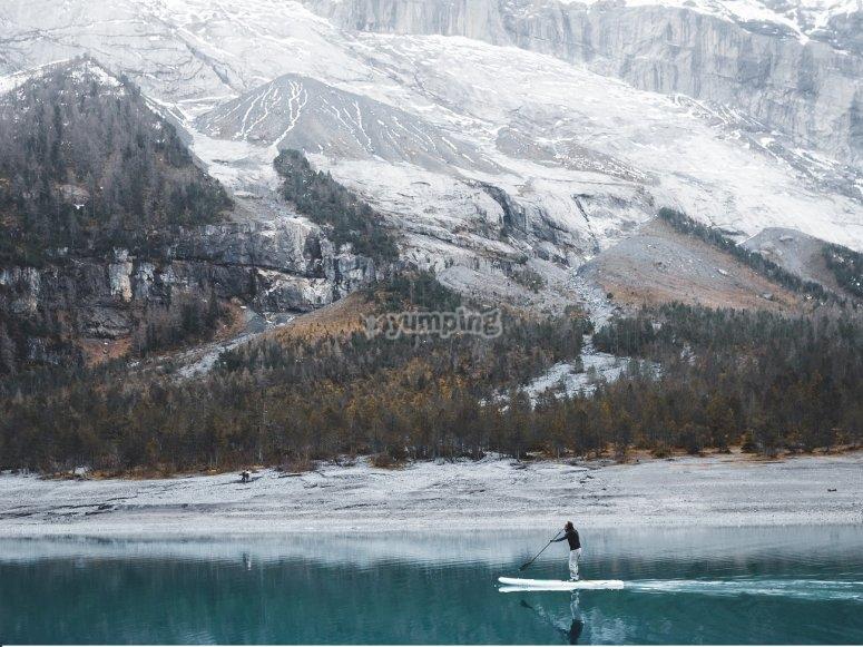 Practicando paddle surf entre montañas nevadas