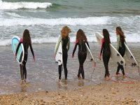 Girls about to enter the sea to surf