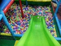 Tobogan verde hasta la piscina de bolas