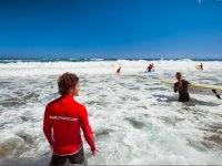 Instructor supervisando a la alumna de surf