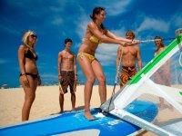 Levantando la vela de windsurf en la arena