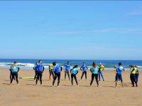 Surfistas calentando en la arena