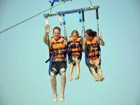 Niño y adultos en parasailing