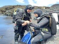 Preparándose en el orilla para la inmersion de buceo