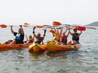 Raising the paddles in three kayaks