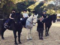 Niñas sobre los caballos junto a la profesora