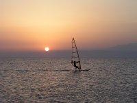 Planche à voile avec le coucher de soleil