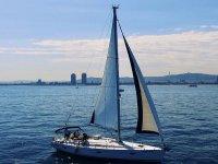 Barca a vela che naviga lungo la costa di Barcellona