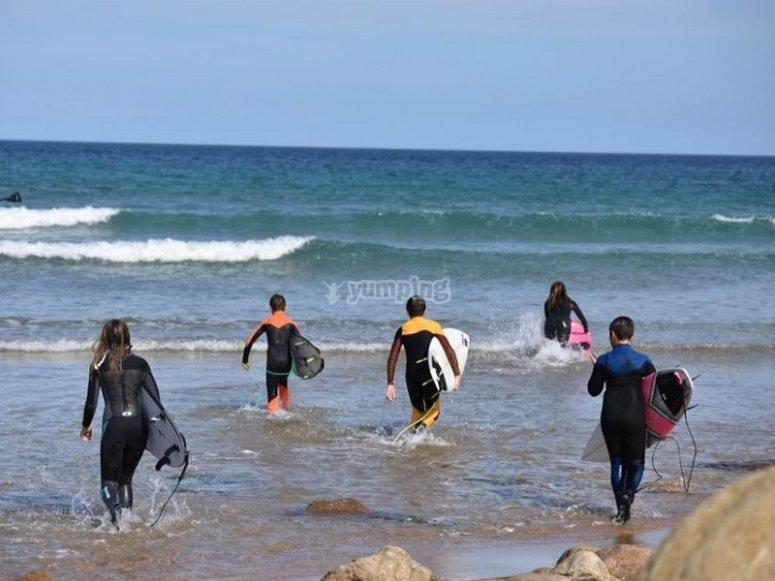 Surfistas entrando al mar