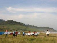 Surfistas en fila llevando las tablas al mar