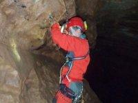 Sujetandose a la pared de la cueva