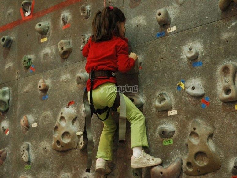 Peque sulla parete di roccia con una felpa rossa