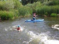 De rodillas haciendo sup en el rio