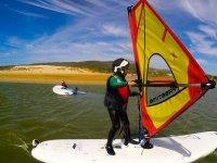 年轻的学生冲浪头盔的背后风帆冲浪的第一步