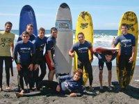 Alumnos de surf con sus tablas en la arena